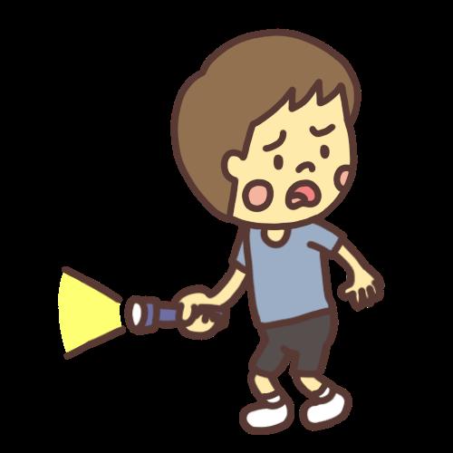 懐中電灯を持って不安そうにお化け屋敷の中を歩く男の子
